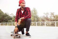 Happy dark skinned young guy sitting near his skateboard Royalty Free Stock Photography