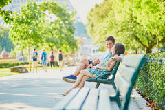 Happy dating couple on a bench in a Parisian park Stock Photography