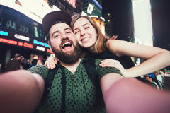 Happy dating couple in love taking selfie photo on Times Square in New York while travel in USA on honeymoon. Happy dating couple in love taking selfie photo on stock images