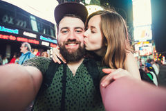 Happy dating couple in love taking selfie photo on Times Square in New York while travel in USA on honeymoon. Happy dating couple in love taking selfie photo on stock photo