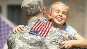 Happy daughter with american flag hugging father in military uniform, homecoming. Stock footage stock video