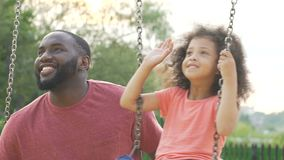 Happy daughter and daddy swinging in yard and waving hands to mom, family
