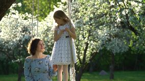 Happy daughter girl pick apple tree bloom and put it into mother hair. Static. Happy daughter girl pick apple tree bloom and put it into mother hair. Family stock footage