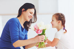 Happy daughter giving mother a spring flower bouquet Royalty Free Stock Images