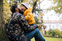 Happy daughter hugging and kissing her dad outside. Family having fun in autumn park. Father`s day, family values stock images