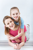 Happy daughter hugging laughing mother on white. Portrait of happy daughter hugging laughing mother on white Stock Photo
