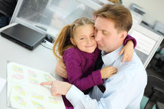 Happy daughter hugs her father who views apartment plan booklet. In office. Focus on girl royalty free stock photos