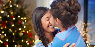 Happy daughter kissing her mother on christmas stock photos