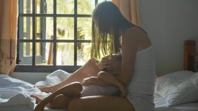 Happy daughter lies on her mother`s lap while she strokes her hair. Royalty Free Stock Photos