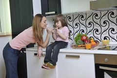 Happy daughter and mom in kitchen Stock Image