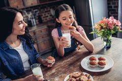 Daughter and mother eating cupcakes stock image