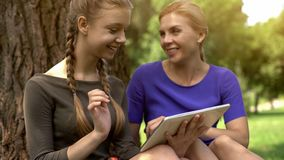 Happy daughter and mother shopping online in park, using tablet, sales in stores. Stock photo stock photography