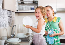Happy daughter with mother washing plates Stock Photos