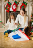 Happy daughter and mother wrapping sweater in wrapping paper at Stock Photo