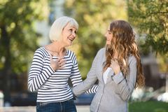 Happy daughter with senior mother walking in park stock photos