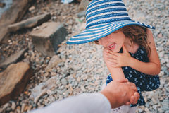 Happy daughter in stripe hat holding mother hand on the beach. Family traveling on summer vacation. Stock Photos
