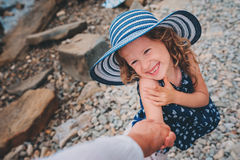 Happy daughter in stripe hat holding mother hand on the beach. Family traveling on summer vacation. Cozy mood, candid shot Stock Images