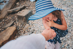 Happy daughter in stripe hat holding mother hand on the beach. Family traveling on summer vacation. Stock Images