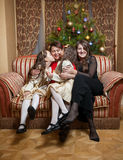 Happy daughters sitting on sofa with mother at christmas Stock Photos