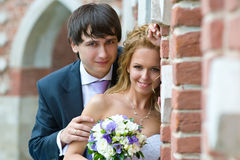 Happy Day. A pair of newlyweds stands near the old brick walls and looks at us happy eyes Stock Photography
