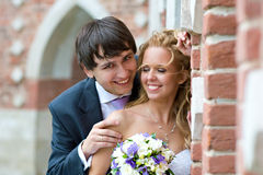 Happy Day_2. A pair of newlyweds stands near the old brick walls, groom looks at us happy eyes, and the bride dropped her lashes down Royalty Free Stock Photos