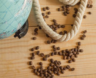 Happy day of conception Columbus. A globe, rope, coffee beans on wooden Board royalty free stock photography
