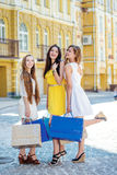 Happy day for girlfriends. Girls holding shopping bags and walk Stock Photos