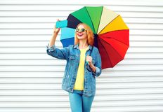 Happy day! smiling woman takes a picture self portrait on smartphone. With colorful umbrella in city on white background stock images