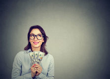 Happy daydreaming business woman with money dollar bills in hand imagining how to spend them. On gray wall background. Financial reward concept Royalty Free Stock Image