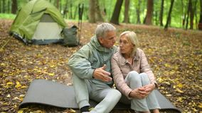 Joyful retired couple resting in the autumn forest. Happy days together. Cheerful retired couple sitting on the mat in the forest and talking while their tent stock video