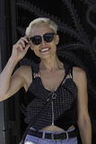 Happy daze in Summer. A platinum blonde woman poses in front of a dark wrought gate stock photo