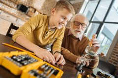 Happy delighted boy learning new skills. New knowledge. Happy delighted nice boy sitting together with his grandfather and smiling while learning new skills Royalty Free Stock Photos