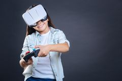 Happy delighted girl playing video games. Modern entertainment. Happy delighted pretty girl holding a game console and playing video games while standing against Royalty Free Stock Images