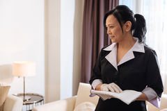 Happy delighted hotel maid standing in the room Stock Photo