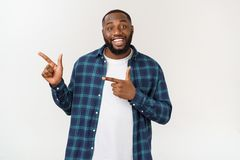 Happy delighted male fore finger at blank copy space, wears denim shirt, has positive smile. Advertisement and ethnicity. Concept royalty free stock photo
