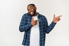 Happy delighted male fore finger at blank copy space, wears denim shirt, has positive smile. Advertisement and ethnicity. Concept stock images