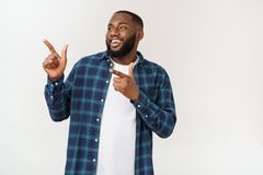 Happy delighted male fore finger at blank copy space, wears denim shirt, has positive smile. Advertisement and ethnicity. Concept stock image
