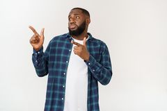 Happy delighted male fore finger at blank copy space, wears denim shirt, has positive smile. Advertisement and ethnicity. Concept stock photography