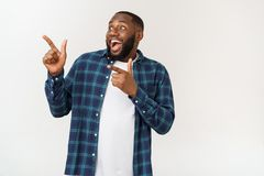 Happy delighted male fore finger at blank copy space, wears denim shirt, has positive smile. Advertisement and ethnicity. Concept royalty free stock image