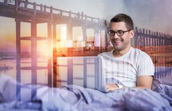 Happy delighted man feeling comfortable. So comfortable. Happy delighted nice man looking at the laptop screen and smiling while feeling comfortable in bed Royalty Free Stock Photography