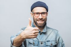 Happy delighted man with stubble raises thumb as shows his approval, dressed in stylish clothing, isolated over white studio back stock photography