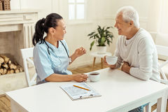 Happy delighted nurse enjoying her tea. Tea time. Happy delighted professional nurse holding a cup and enjoying tea while talking to her patient Royalty Free Stock Photography