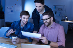 Happy delighted programmers enjoying their work. We love our job. Happy delighted handsome programmers looking at the sheet of paper and smiling while enjoying Royalty Free Stock Photography