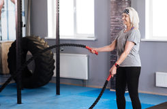 Happy delighted woman holding ropes. Pleasurable activity. Happy delighted elderly woman holding ropes and exercising  them while enjoying the activity Royalty Free Stock Image