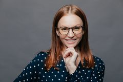 Happy delighted young woman keeps one hand under chin, smiles happily, wears transparent glasses, elegant clohtes, has eyes full royalty free stock image