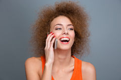 Happy delightful curly woman talking on mobile phone and laughing Stock Photos