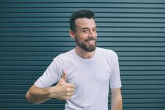 Happy and delightful man is showing his big thumb up. Also guy is looking at camera and smiling. He is posing. Isolated stock photography