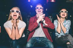 Happy and delightful people are sitting together and watching movie with pleasure. Each of them are keeping their hands stock image