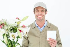 Happy delivery man with bouquet showing blank note Royalty Free Stock Photo