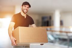 Happy delivery man with box. In business center Royalty Free Stock Photo